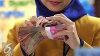 Petugas Bank menghitung uang pecahan Rp100.000 di Bank Bukopin Syariah, Jakarta, Selasa (29/12). Di pasar spot, Senin (28/12), rupiah melemah tipis 0,08% ke Rp 13.642 per dollar AS. (Liputan6.com/Angga Yuniar)