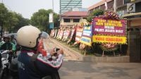 Warga mengabadikan karangan bunga di Halaman Polres Jakarta Barat, Jumat (23/11). Puluhan karangan bunga yang dikirimkan warga tersebut diberikan guna mendukung kepolisian dalam memberantas aksi premanisme di Jakarta Barat. (Liputan6.com/Faizal Fanani)