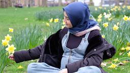Ratna Galih tengah menikmati suasana taman dengan duduk sambil memperhatikan bunga warna kuning. Dengan memakai setelah hitam dan rompi jeans, Ratna terlihat begitu stylish. Hamil besar, tampaknya bukan penghalang Ratna untuk tampil trendi (Liputan6.com/IG/@ratnagalih)