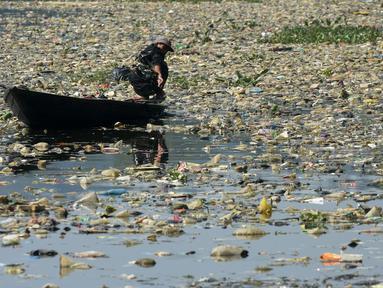 Warga menggunakan perahu untuk memilah sampah plastik di aliran Sungai Citarum, Bandung, Jawa Barat, Rabu (26/6/2019). Berbagai upaya dilakukan pemerintah untuk membersihkan sungai yang menyandang predikat salah satu tempat paling tercemar di dunia ini. (Timur Matahari/AFP)