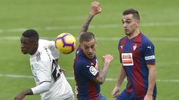 Striker Real Madrid, Vinicius Junior, berebut bola dengan gelandang Eibar, Ruben Pena, pada laga La Liga di Stadion Ipurua, Eibar, Sabtu (24/11). Eibar menang 3-0 atas Madrid. (AFP/Ander Gillenea)
