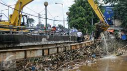 Petugas Sudin Kebersihan DKI Jakarta menurunkan alat berat untuk mengangkut sampah yang menumpuk di jembatan Kampung Melayu, Jatinegara, Jakarta Timur, Minggu (3/4/2016). (Liputan6.com/Yoppy Renato)