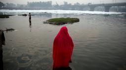 Pemuja Hindu berdoa sambil berdiri di perairan Sungai Yamuna selama Festival Chhath di New Delhi, India, Selasa (13/11). Festival Hindu kuno ini dilakukan sebagai bentuk terima kasih kepada Dewa Matahari yang menopang kehidupan di bumi. (AP/Altaf Qadri)