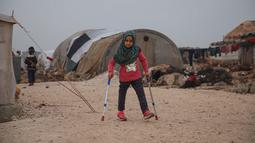 Bocah Suriah, Maya Merhi berjalan dengan kaki prostetik dibantu tongkat kruk di kamp Serjilla, 9 Desember 2018. Gadis 8 tahun itu kini bisa berjalan menggunakan kaki prostetik baru atau kaki buatan setelah menjalani perawatan di Turki. (Aaref WATAD/AFP)