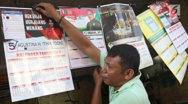 Pekerja menunjukkan kalender tahun 2019 di kawasan Senen, Jakarta, Jumat (7/12). Menjelang berakhirnya tahun 2018, produksi kalender di kawasan pusat percetakan tersebut meningkat 40 persen. (Liputan6.com/Immanuel Antonius)