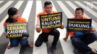 Aktivis mengangkat tulisan bertema satir usai memparodikan adegan pertemuan anggota Pansus Hak Angket KPK dengan narapidana kasus korupsi di depan Gedung KPK, Jakarta, Minggu (9/7). Mereka mengkritisi pertemuan tersebut. (Liputan6.com/Helmi Fithriansyah)