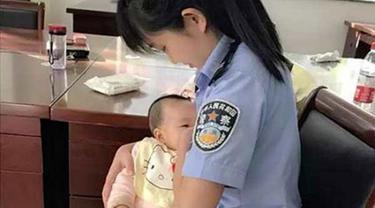 Seorang petugas pengadilan menyusui anak perempuan yang tengah diadili. (China Daily/Asia News Network)