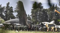 Petugas keamanan dan tim penyelamat berjaga di sekitar reruntuhan pesawat tentara Aljazair yang jatuh di dekat pangkalan udara Boufarik, Aljazair (11/4). (AFP Photo/Ryad Krmadi)