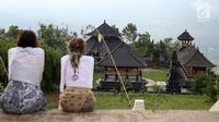 Wisatawan menikmati suasana di Pelataran Agung Pura Lempuyang, Karangasem, Bali, Kamis (7/12). Erupsi Gunung Agung menyebabkan sejumlah destinasi wisata di kawasan Bali Timur mengalami penurunan jumlah wisatawan. (Liputan6.com/Immanuel Antonius)