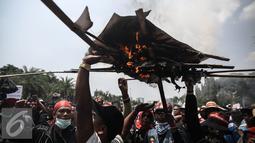 Massa aksi membakar poster saat berlangsungnya unjuk rasa memperingati hari Nelayan Nasional didepan Istana Merdeka, Jakarta, Rabu (6/4). Dalam aksinya mereka meminta pemerintah menghapus Permen tentang transhipment. (Liputan6.com/Faizal Fanani)