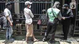 Petugas memeriksa suhu tubuh warga sebelum memasuki area layanan makan gratis di Jalan Basuki Rachmat, Cipinang Muara, Jakarta, Senin (8/3/2021). Sebagian besar yang datang mayoritas berprofesi kuli bangunan, pengamen, petugas taman kota hingga pengemudi ojek online. (merdeka.com/Iqbal S Nugroho)