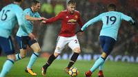 Pemain Manchester United Luke Shaw berebut bola dengan pemain AFC Bournemouth, Junior Stanislas pada lanjutan laga Premier League di Old Trafford, Rabu (13/12). Romelu Lukaku menjadi penentu kemenangan dengan skor 1-0 itu. (Oli SCARFF / AFP)