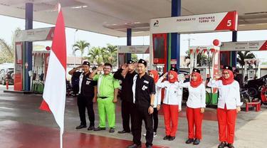 SPBU Cikini 3110303, sebagian Operator SPBU melaksanakan upacara bendera tanpa meninggalkan kewajibannya melayani BBM bagi masyarakat.