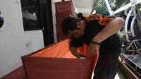 Petugas menyelesaikan pembuatan peti mati khusus jenazah virus corona atau Covid-19 di Dinas Pertamanan dan Pemakaman Jakarta, Sabtu (28/3/2020). Peti mati korban meninggal akibat corona Covid-19 itu dilapisi kantong jenazah dan kain kafan untuk mencegah penyebaran virus. (Liputan6.com/Angga Yuniar)