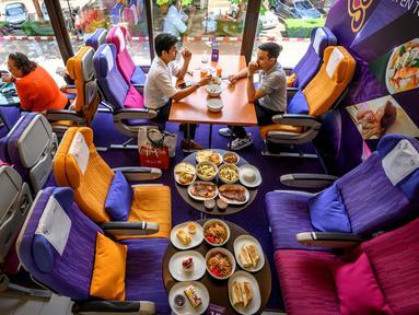 Orang-orang duduk di kursi pesawat saat makan di restoran pop-up bertema kabin pesawat di kantor pusat Thai Airways di Bangkok, 10 September 2020. Restoran pop-up ini menyajikan sekitar 2.000 makanan per hari untuk memulihkan pendapatan yang hilang selama pandemi virus corona. (Mladen ANTONOV/AFP)