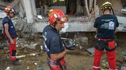 Anggota dari Pemadam Kebakaran Darurat Internasional Prancis bersiap memasuki hotel Mercure untuk mencari korban gempa dan tsunami di Palu, Sulteng (4/10). Sebanyak 1.411 orang telah dikonfirmasi tewas akibat bencana tersebut. (AFP Photo/Mohd Rasfan)