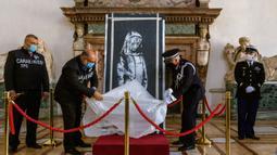Lukisan seniman Inggris Banksy yang menggambarkan sosok perempuan muda dengan ekspresi sedih sebagai penghormatan kepada para korban serangan teror 2015 dikembalikan oleh jaksa Italia ke Prancis di Kedutaan Besar Prancis di Roma (14/7/2020). (AP/Photo/Domenico Stinellis)