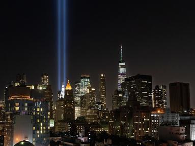 Instalasi cahaya bertajuk 'Tribute in Light'  menerangi langit di lower Manhattan, New York, Selasa (10/9/2019). Cahaya kembar berwarna biru tersebut dinyalakan untuk memperingati 18 tahun peristiwa serangan gedung kembar World Trade Center (WTC)  pada 11 September 2001 silam. (AP/Mark Lennihan)