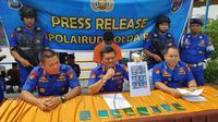 Direktur Polisi Air Polda Riau memperlihatkan foto TKI ilegal yang diselundupkan warga Bengkalis ke Indonesia. (Liputan6.com/M Syukur)