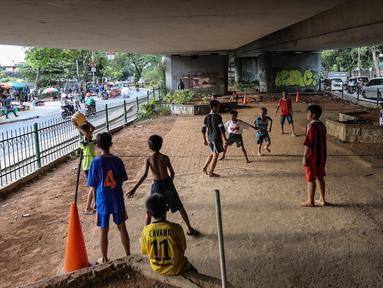 Anak-anak bermain sepak bola di kolong jembatan layang Tanah Abang, Jakarta, Kamis (15/11). Mereka memanfaatkan lahan kosong usai jam pulang sekolah. (Liputan6.com/Fery Pradolo)