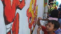 Anak-anak melukis mural pada dinding areal gang sempit saat kegiatan kick off Kampung Mural di Pulo Gelis, Bogor, Minggu (18/3). Kegiatan ini untuk menjadikan Kampung Pulo Geulis sebagai salah satu tujuan wisata baru di Bogor. (Merdeka.com/Arie Basuki)