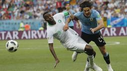 Pemain Uruguay, Edinson Cavani (kanan) berebut bola dengan pemain Arab Saudi, Osama Hawsawi pada laga grup A Piala Dunia 2018 di Rostov Arena, Rostov-on-Don, Rusia, (20/6/2018). Uruguay menang 1-0. (AP/Darko Vojinovic)