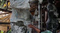 Sutopo membuat pesanan patung di kawasan Pondok Cabe, Tangsel, Jumat (14/12). Pembuatan patung beragam dari bahan perunggu hingga cetakan semen, Harga pembuatannya juga beragam sesuai tingkat kesulitan dan bahan yang dipakai. (Liputan6.com/Faizal Fanani)
