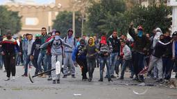 Para pengunjuk rasa melakukan aksi protes di luar kantor pemerintah setempat di Kasserine, Tunisia, Kamis (21/1). Para pengangguran muda turun ke jalan memprotes keterpurukan ekonomi dan sulitnya lapangan kerja. (REUTERS/Amine Ben Aziza)