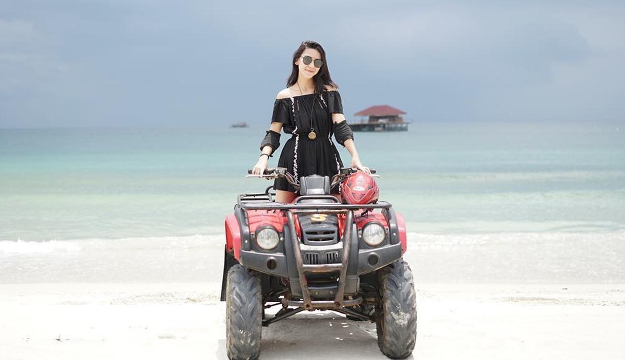 """Di tengah kesibukannya sebagai selebriti, pemeran Vira di program """"The East"""" ini menyempatkan waktunya untuk pergi berlibur di Pantai Lagoi Bintan, Kepulauan Riau. Ia pun menikmati hamparan pasir putih sambil mengendari ATV. (Liputan6.com/IG/adindathomas)"""