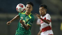 Gelandang Persebaya Surabaya, Koko Ari (kiri) berebut bola dengan striker Madura United, Mochammad Kevy dalam laga matchday ke-2 Grup C Piala Menpora 2021 di Stadion Si Jalak Harupat, Bandung, Minggu (28/3/2021). (Bola.com/M Iqbal Ichsan)