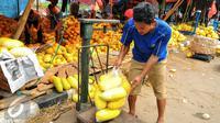 Pedagang menimbang timun suri yang akan dijual kepada pembeli di Pasar Kramat Jati, Jakarta, Senin (14/6/2016). (Liputan6.com/Yoppy Renato)