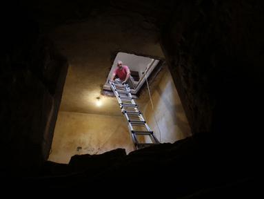 Tal menurunkan tangga ke lorong yang terdapat kolam ritual Yahudi (Mikveh) yang ditemukan di rumahnya, Ein Karem, Yerusalem (1/7/2015). Tal menemukan Mikveh yang diyakini berusia lebih dari 2.000 tahun saat sedang merenovasi rumah.  (AFP/GALI TIBBON)