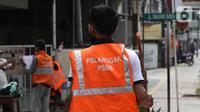 Warga pelanggar PSBB dihukum menyapu saat terjaring razia masker di Jalan Tanjung Duren Raya, Jakarta, Jumat (11/9/2020). Petugas Satpol PP gencar melakukan razia masker menyusul kasus COVID-19 di DKI Jakarta yang terus meningkat. (merdeka.com/Imam Buhori)