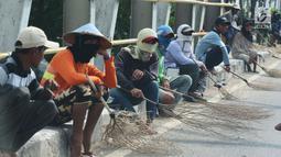 Sejumlah penyapu koin duduk sambil menunggu koin yang dilempar ke jalan di kawasana Subang, Jawa Barat, Sabtu (7/1). Pasca Lebaran warga yang menjadi penyapu uang koin menjadi banyak dibanding hari biasanya. (Liputan6.com/Helmi Afandi)