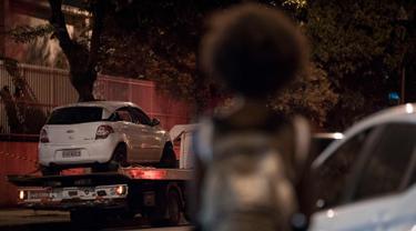 Seorang warga melihat mobil politisi Brasil Marielle Franco yang ditembak di Rio de Janeiro, Brasil (15/3). Penembakan mobil putih tersebut menewaskan Marielle Franco dan sopirnya. (AFP Photo/Mauro Pimentel)