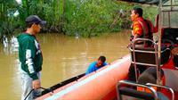 Personel Basarnas dibantu warga mencari wanita diterkam buaya di Sungai Indragiri. (Liputan6.com/Dok Basarnas Pekanbaru/M Syukur)