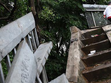 Pejalan kaki melintasi JPO yang rusak di Terminal Kampung Rambutan, Jakarta, Senin (28/1). Kondisi JPO yang sebagian pagar pembatasnya rusak tersebut membahayakan pejalan kaki apabila tidak segera diperbaiki. (Liputan6.com/Immanuel Antonius)
