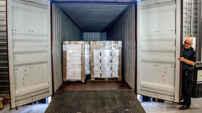 Seorang petugas bea cukai Belanda menampilkan sebuah kontainer berisi 90.000 botol vodka. (Robin Utrecht / AFP)