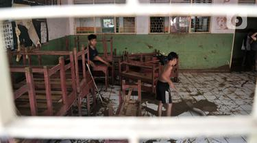 Siswa membantu membersihkan lumpur sisa banjir di SD-SMP Perguruan Rakyat 2, Kampung Melayu Kecil, Kelurahan Bukit Duri, Kecamatan Tebet, Jakarta Selatan, Senin (6/1/2020). (merdeka.com/Iqbal S. Nugroho)