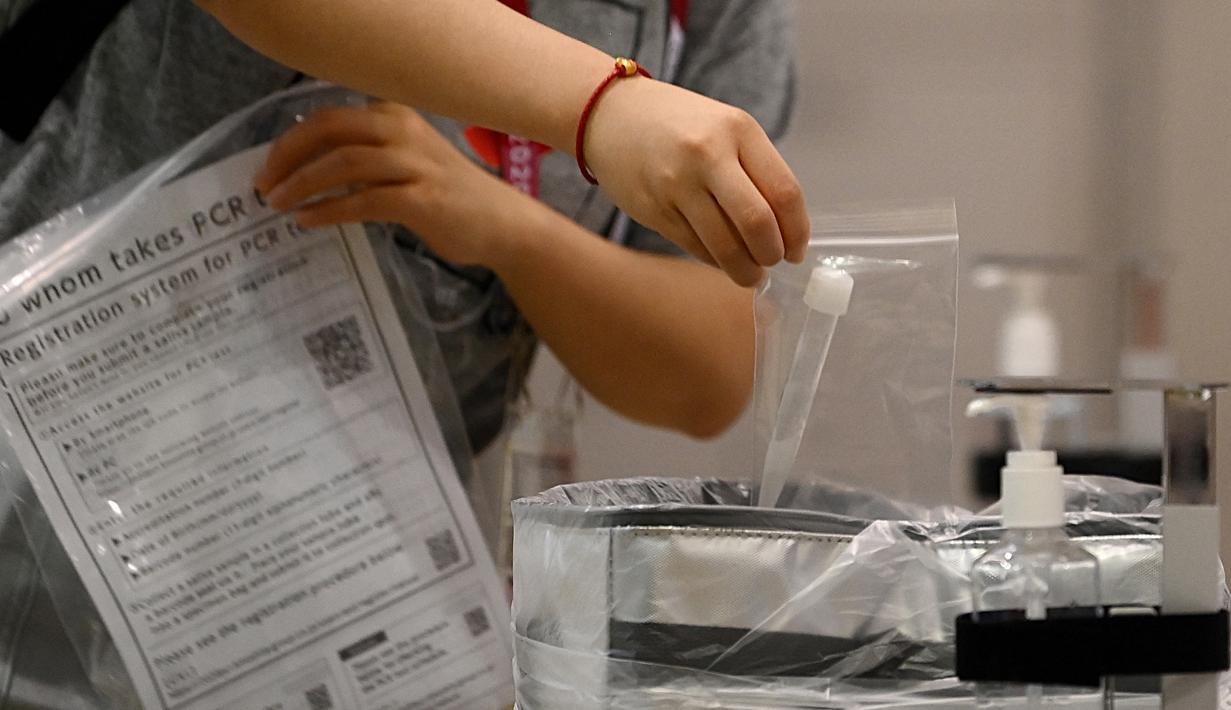 Seorang jurnalis menaruh sampel air liur harian saat tes PCR di Pusat Media Olimpiade Tokyo 2020, Tokyo, Jepang, 20 Juli 2021. Jurnalis seluruh dunia tiba di Jepang untuk meliput Olimpiade Tokyo 2020 di tengah kungkungan pandemi COVID-19. (Franck FIFE/AFP)