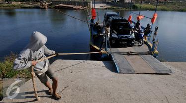 Pekerja menarik perahu eretan berisi kendaraan menyebrangi Sungai Citarum di Muara Gembong, Bekasi, Rabu, (29/7/2015). Kendaraan yang menyebrang menggunakan perahu eretan dikenakan biaya Rp.20.000 bagi mobil dan Rp 2.000 motor. (Liputan6.com/Johan Tallo)