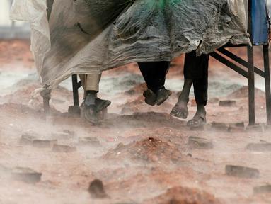 Pekerja migran India menutupi diri mereka dengan selembar plastik selama hujan di tempat pembakaran batu bata di pinggiran Kathmandu. Ribuan pekerja migran India datang ke Nepal untuk bekerja di pabrik batu bata. (AP Photo/Niranjan Shrestha)