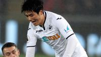 Pemain Arsenal, Aaron Ramsey berebut bola dengan pemain Swansea City, Ki Sung-yueng dalam laga pekan ke-25 Premier League 2017-2018 di Liberty Stadium, Selasa (30/1). Arsenal dipaksa menyerah Swansea City 1-3. (Nick Potts/PA via AP)