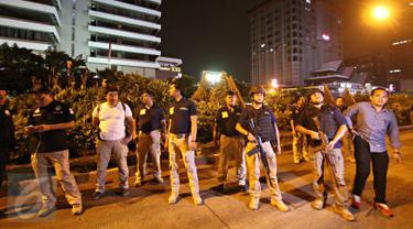 Sejumlah polisi berjaga di area gedung Jaya, Jalan MH Thamrin, Jakarta Pusat, Kamis (14/1). Ledakan yang diduga berasal dari ban truk yang pecah itu sempat membuat Jalan MH Thamrin kembali ditutup pada malam hari. (Liputan6.com/Immanuel Antonius)