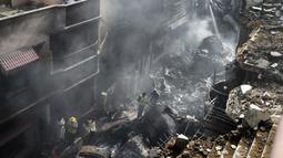 Petugas penyelamat berkumpul di lokasi jatuhnya pesawat Pakistan International Airlines di Karachi, Pakistan, Jumat (22/5/2020). Proses evakuasi baru berakhir pada Sabtu dini hari. (Rizwan TABASSUM/AFP)