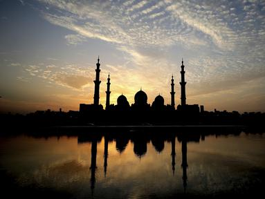 Matahari terbenam di belakang Masjid Agung Sheikh Zayed di Abu Dhabi, Uni Emirat Arab (8/11/2019). Masjid ini adalah masjid terbesar ketiga di dunia setelah masjid di Mekkah dan Madinnah. (AFP Photo/Kamran Jebreili)
