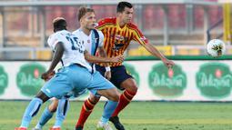 Pemain Lecce, Nehuen Paz, berebut bola dengan pemain Lazio, Ciro Immobile, pada laga Serie A di Stadion del Mare, Selasa (7/7/2020). Lecce menang 2-1 atas Lazio. (Donato Fasano/LaPresse via AP)