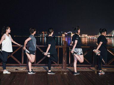 Anggota klub lari merenggangkan tubuh usai berlari di malam hari di Taman Wanlu di Haikou, Provinsi Hainan, China selatan, pada 28 Mei 2020. Berlari di malam hari menjadi olahraga yang populer di kalangan warga Haikou. (Xinhua/Pu Xiaoxu)