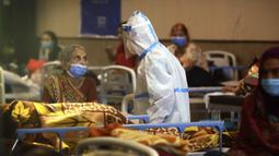 Petugas kesehatan berbicara dengan seorang wanita di pusat karantina untuk pasien COVID-19 di New Delhi, India, Senin (19/4/2021). Pihak berwenang mengatakan pada hari Senin bahwa rumah sakit telah didorong hingga batasnya. (AP Photo/Manish Swarup)
