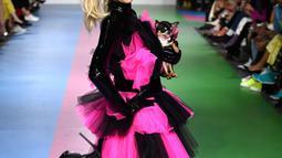 Paris Hilton membawa anjing saat tampil dalam Christian Cowan x The Powerpuff Girls Fashion Show, Los Angeles, AS, Jumat (8/3). Anjing tersebut terlihat seperti putri raja dengan simpul besar di tubuhnya. (Frazer Harrison/Getty Images North America/AFP)